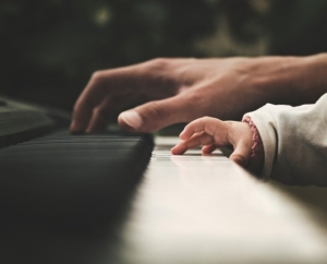 パパと一緒にピアノの鍵盤に触る赤ちゃんの指