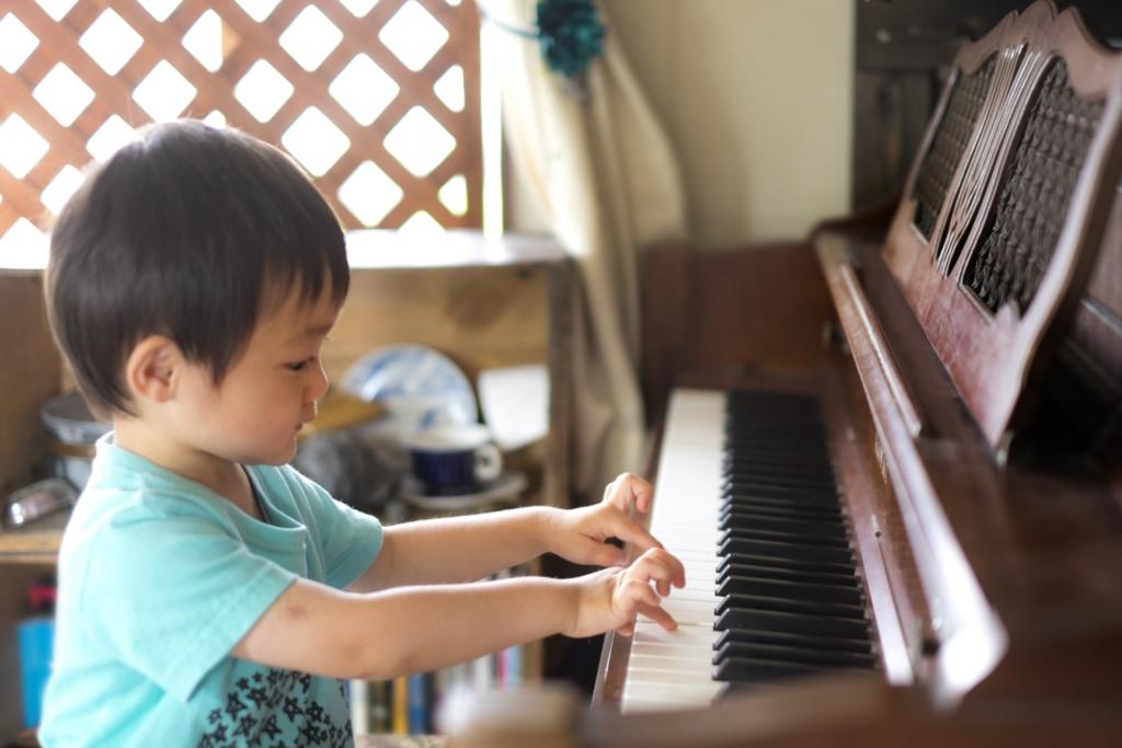 小さな男の子がピアノを弾いている