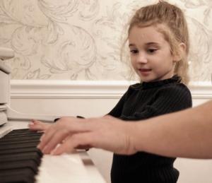 レッスンを受けて楽しそうにピアノを弾く女の子