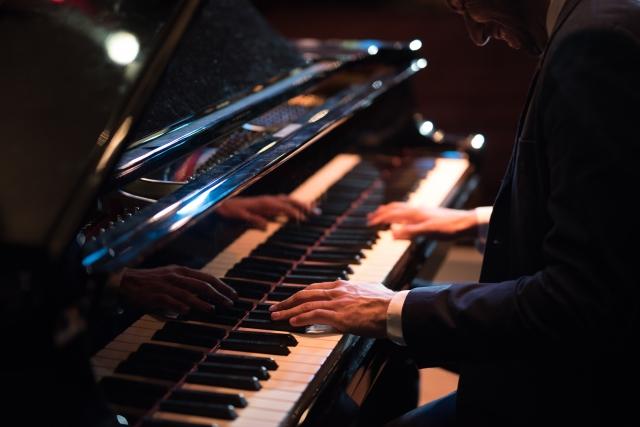 ステージでピアノを弾くタキシード姿の男性