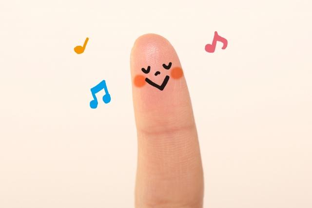 指先がニコニコ笑って音符が飛んでいる