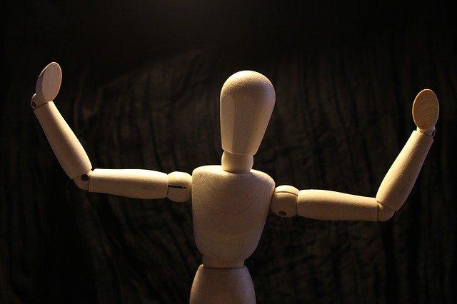 腕を大きく上げた木の人形