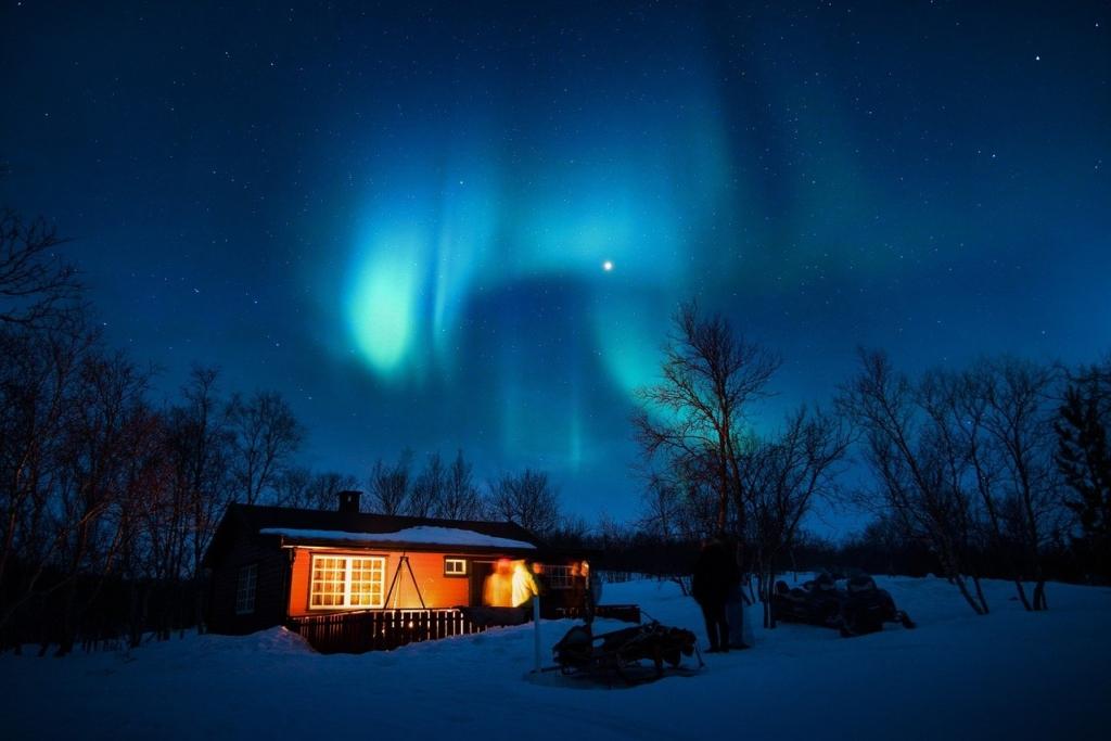 ネイビーの空に浮かぶオーロラと灯りの灯る家