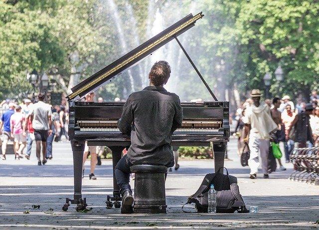 公園でピアノを弾く男性の後ろ姿