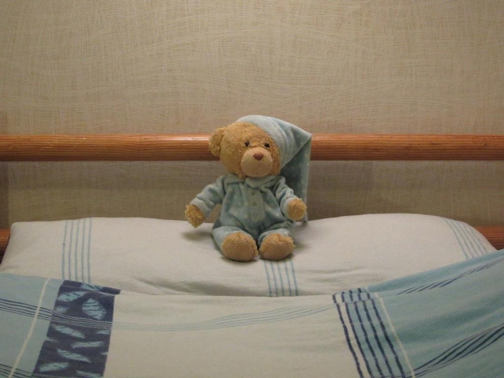 ベッドに居るクマのぬいぐるみ